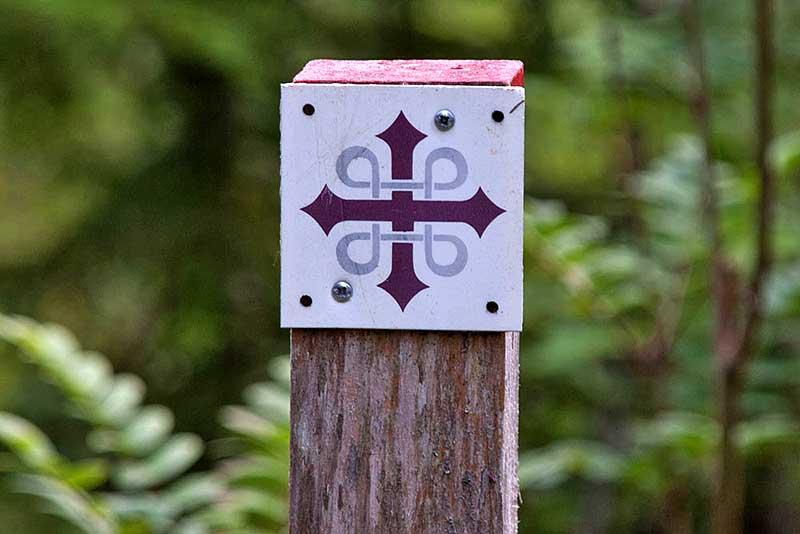 Rotes Olavskreuz  durchflochten von Schleifenquadrat Symbol des Olavsweges